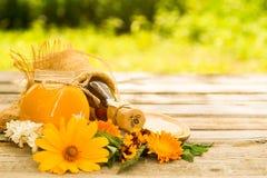 在玻璃瓶子的蜂蜜有花背景 免版税图库摄影