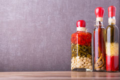 在玻璃瓶子的被保存的食物,在一个木架子 各种各样的用卤汁泡的食物 免版税图库摄影