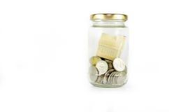 在玻璃瓶子里面的微型房子用在白色背景隔绝的硬币填装了 库存照片