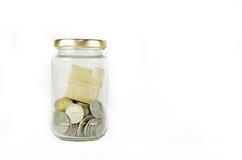 在玻璃瓶子里面的微型房子用在白色背景隔绝的硬币填装了 免版税库存照片
