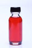 在玻璃瓶白色盖帽的红色液体 库存照片