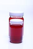 在玻璃瓶白色盖帽的红色液体 免版税库存照片