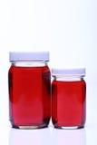 在玻璃瓶白色盖帽的红色液体 库存图片