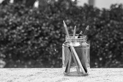在玻璃瓶的各种各样的铅笔在水泥地板上有绿色灌木背景 免版税库存图片