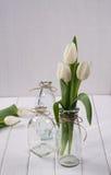 在玻璃瓶的白色郁金香 免版税库存照片