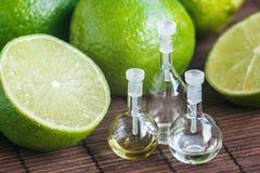 在玻璃瓶的精油有新鲜,水多,成熟石灰的 浴秀丽构成油用肥皂擦洗处理 温泉概念 免版税库存照片