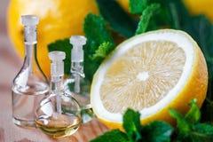 在玻璃瓶的精油用新鲜,水多的柠檬果子和薄菏绿色叶子在木背景的 浴秀丽构成油用肥皂擦洗处理 免版税库存图片