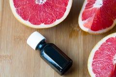 在玻璃瓶的精油用新鲜,水多的葡萄柚 温泉概念 库存照片