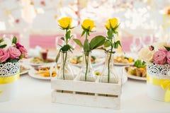 在玻璃的三朵tellow玫瑰在花梢装饰的桌上vasen 免版税库存照片