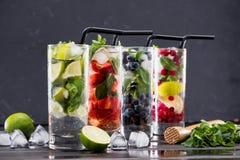 在玻璃的不同的新鲜的柠檬水与冰块 库存照片