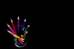在玻璃的五颜六色的铅笔在黑ckground 免版税库存图片