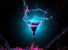 在玻璃的五颜六色的鸡尾酒与飞溅 库存照片