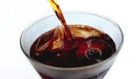 在玻璃的倾吐的可乐在被隔绝的背景 股票录像