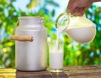 在玻璃的倾吐的牛奶。 免版税库存图片