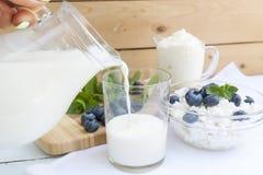 在玻璃的倾吐的牛奶在桌上 图库摄影