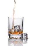 在玻璃的倾吐的苏格兰威士忌酒与冰块 免版税库存照片