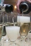 在玻璃的倾吐的香槟 库存图片