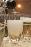在玻璃的倾吐的香槟 免版税库存照片