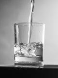 在玻璃的倾吐的水 免版税图库摄影