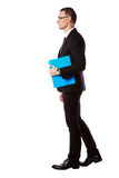在玻璃的商人与蓝色文件夹 免版税库存照片