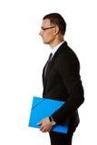 在玻璃的商人与蓝色文件夹 库存图片