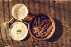 在玻璃的啤酒,油煎方型小面包片和garlick调味 啤酒和快餐对啤酒 免版税库存图片