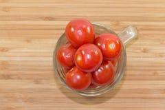 在玻璃的小未加工的蕃茄在木背景 免版税图库摄影