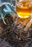 在玻璃的干黑茉莉花茶在木背景 免版税库存照片