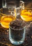 在玻璃的干黑茉莉花茶在木背景 库存照片