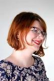 在玻璃的微笑的红头发人在花服 免版税库存图片