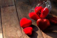 在玻璃的心脏在木背景 免版税库存照片