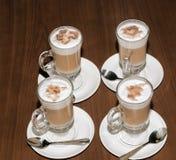 在玻璃的新鲜的热奶咖啡在棕色木桌上 免版税图库摄影