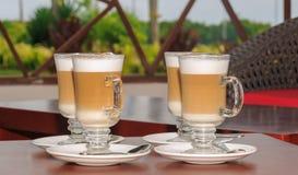在玻璃的新鲜的热奶咖啡在棕色木桌上 库存图片