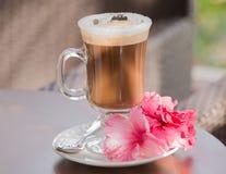 在玻璃的新鲜的热的热奶咖啡在木桌上 免版税库存照片