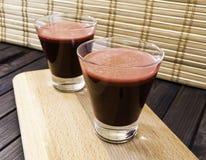 在玻璃的新鲜的红萝卜和甜菜根汁在被定调子的木盘子和竹子背景选择聚焦 库存照片