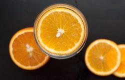 在玻璃的橙色切片,从上面的看法,在黑木背景,特写镜头, 免版税库存图片