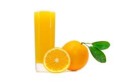 在玻璃的橙色新鲜的汁液用与在白色和切的桔子的整个桔子隔绝的叶子 免版税库存照片