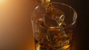 在玻璃的男服务员倾吐的威士忌酒与反射,温暖的晚上大气, 影视素材