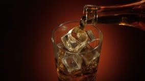 在玻璃的男服务员倾吐的威士忌酒在与反射,温暖的晚上大气的桌上, 影视素材