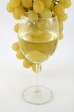 在玻璃的白葡萄酒在葡萄下 库存图片