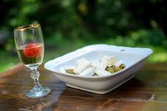 在玻璃的白葡萄酒用草莓、橄榄和乳酪在白色碗 免版税库存照片