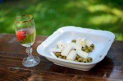 在玻璃的白葡萄酒用草莓、橄榄和乳酪在白色碗 免版税图库摄影