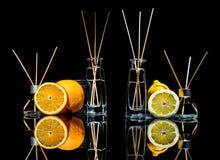 在玻璃的空气清新剂刺激用在黑背景和柠檬、绿色苹果和桔子与反射隔绝的棍子 库存照片