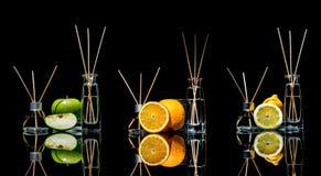 在玻璃的空气清新剂刺激用在黑背景和柠檬、绿色苹果和桔子与反射隔绝的棍子 图库摄影
