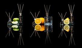 在玻璃的空气清新剂刺激用在黑色和柠檬、绿色苹果和桔子与反射隔绝的棍子 免版税库存图片