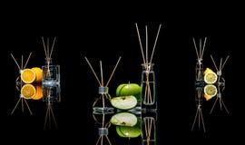在玻璃的空气清新剂刺激用在黑色和柠檬、绿色苹果和桔子与反射隔绝的棍子 图库摄影