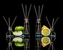在玻璃的空气清新剂刺激用棍子和柠檬,在黑色与反射的绿色苹果隔绝的 库存照片