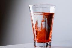 在玻璃的红色泼溅物 免版税库存照片
