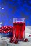 在玻璃的红色蔓越橘汁,在蓝色黏土的蔓越桔鞠躬 免版税库存图片