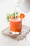 在玻璃的红萝卜汁和倾吐的牛奶 库存图片